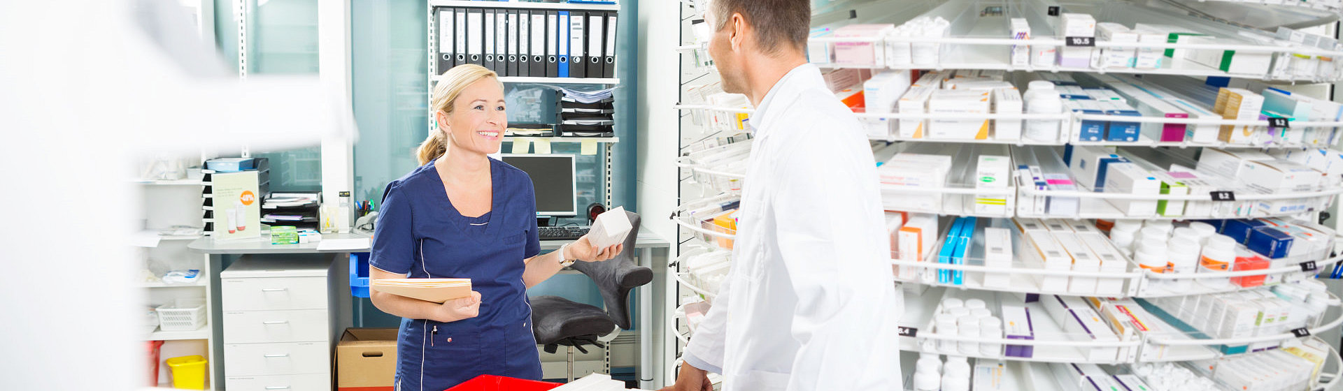 Pharmacist and assistant counting stock in pharmacy